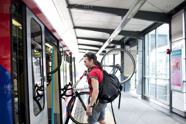 Cyclist boarding subway train with his bicycle