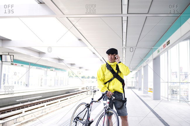 Cyclist talking on his phone in a subway station