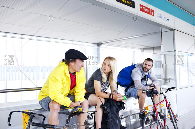 Three cyclists sitting in a subway station