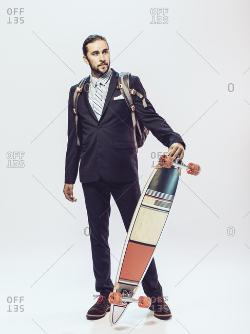 Young man in a suit propping up a skateboard