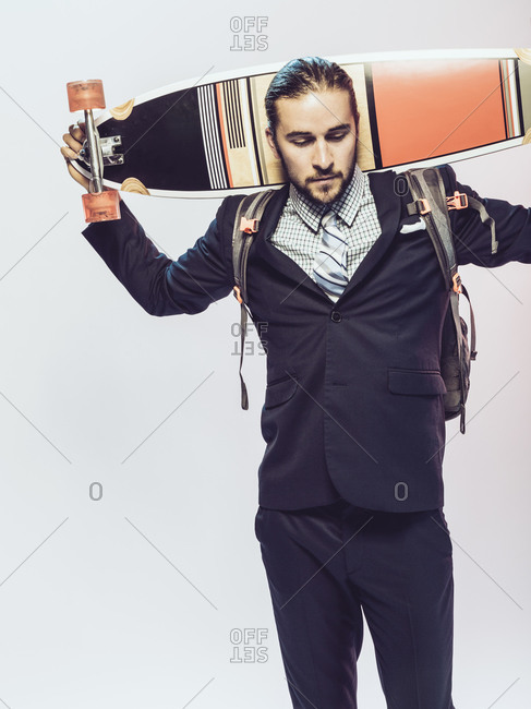 Man in a suit holding a skateboard behind his head