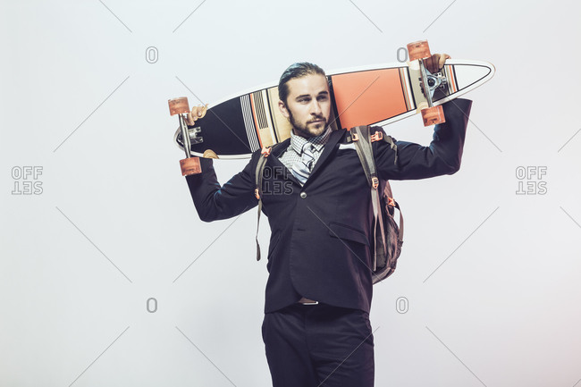 Man in a suit holding a skateboard on his shoulders