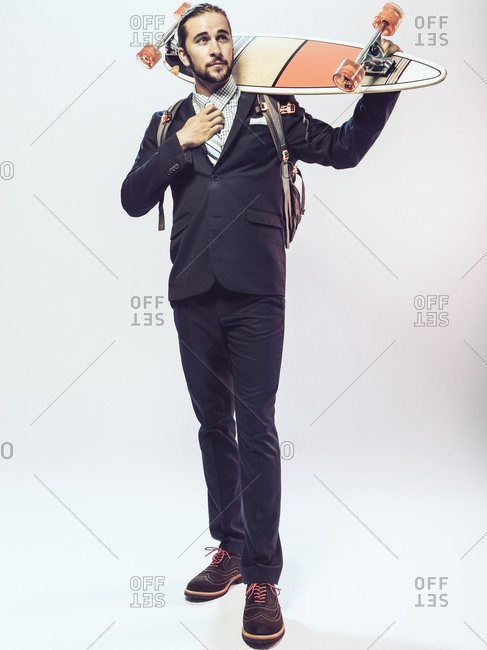 Man in a suit adjusting tie and holding a skateboard