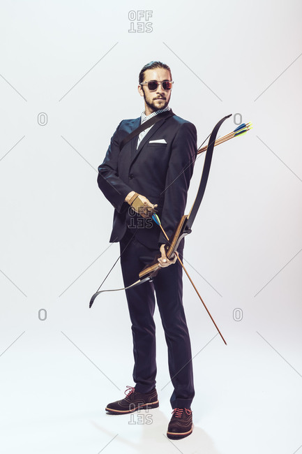 Young man in a suit holding a bow and arrow