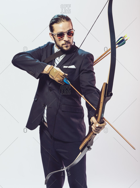 Young man in a suit aiming a bow and arrow