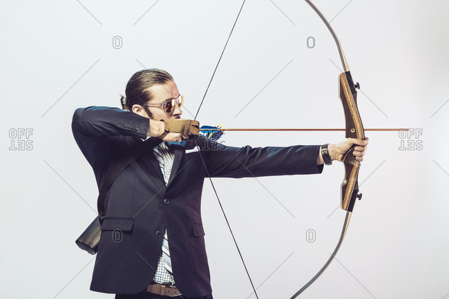Man in a suit aiming an arrow