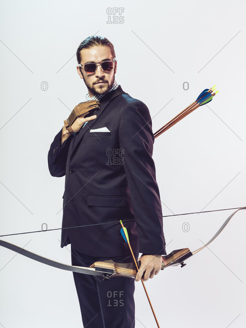 Young man in a suit with a bow and arrow adjusting his tie