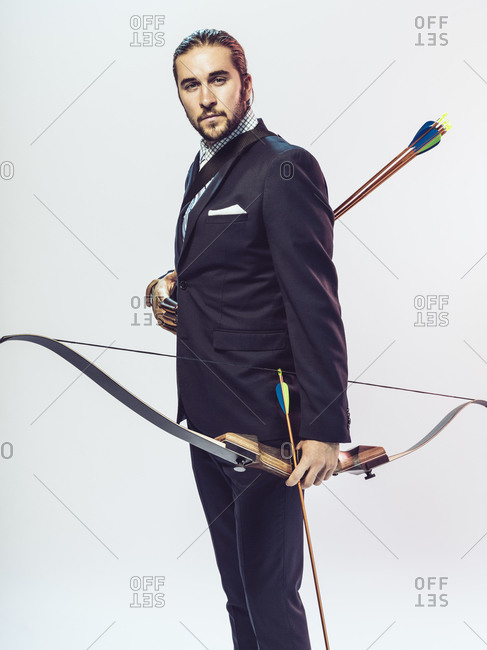 Young man in formal wear holding a bow and arrow