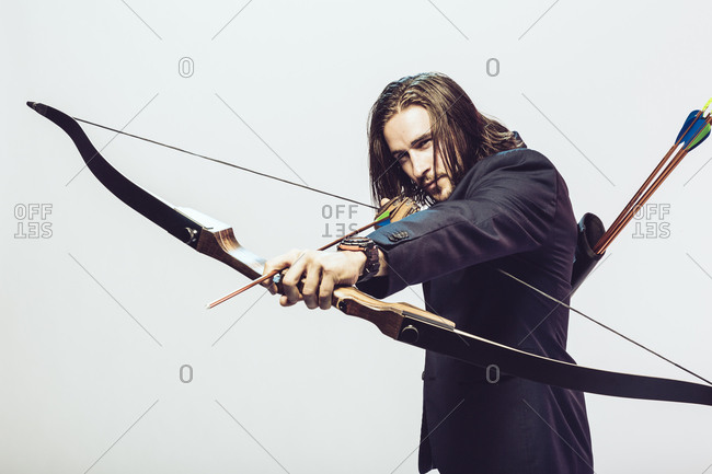 Young man in formal wear aiming a bow and arrow
