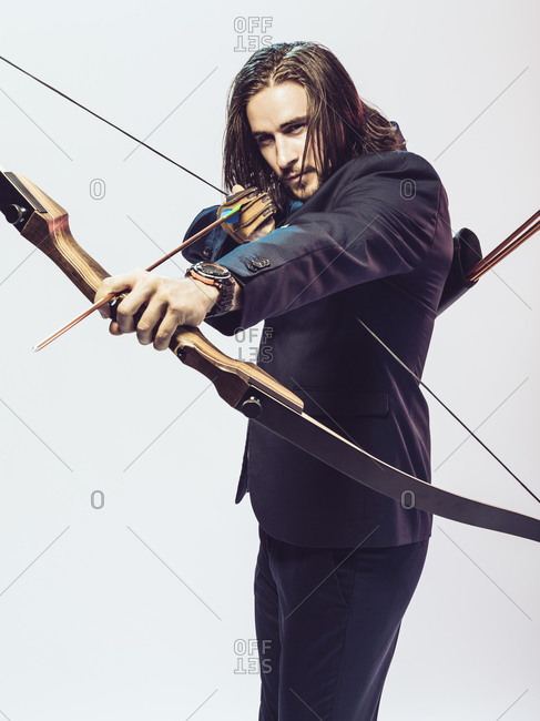 Young man in formal wear aiming an arrow