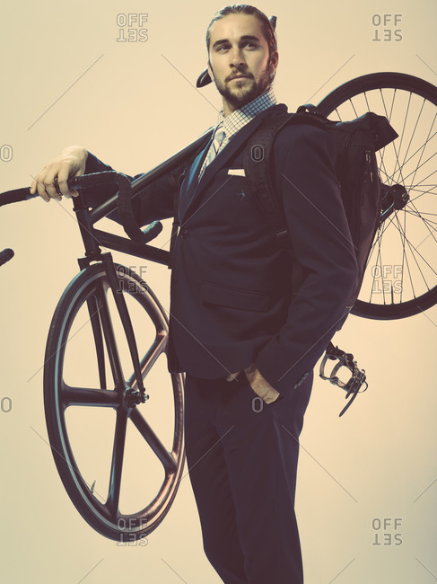 Young man in a suit holding a bicycle on his shoulder
