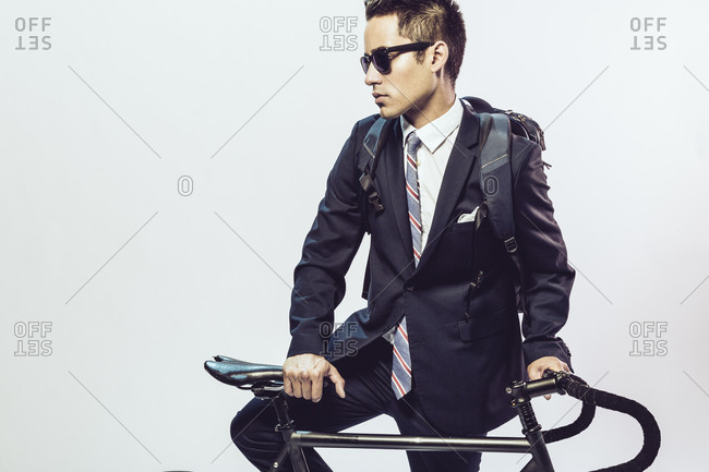 Young man in a suit propped on a bicycle