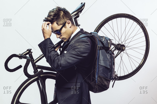 Young man in formal wear carrying a bike and fixing his hair