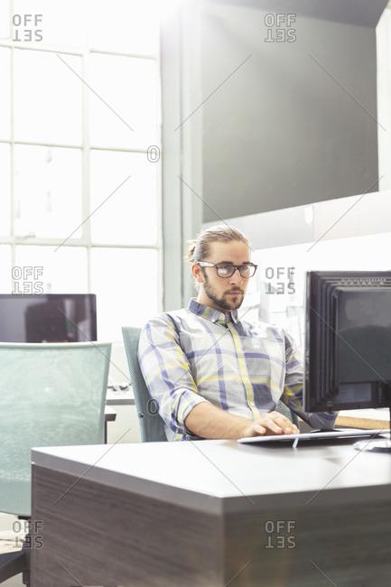 Young man sitting at a desktop computer