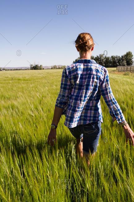 Young woman walking through a tall field