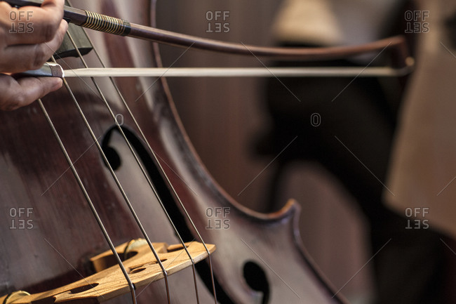 Hand pulling a bow across a cello