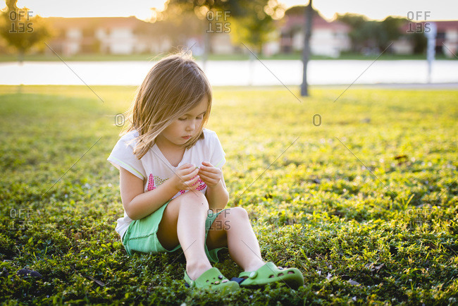 Young girl sitting outside on grass examining a leaf