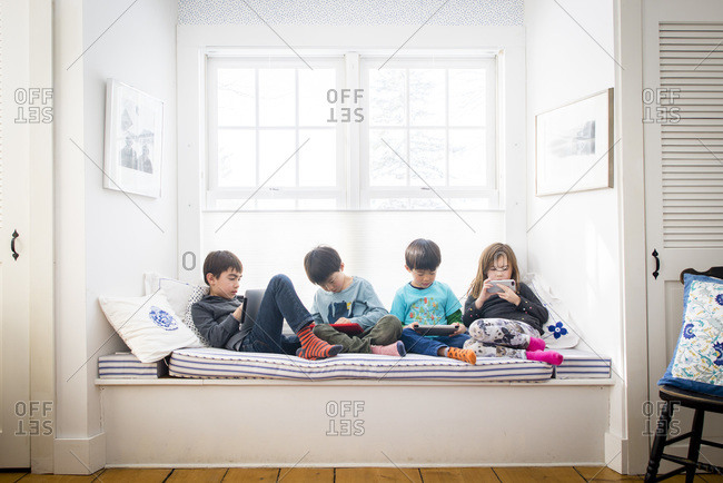 Four children relax with electronic devices on window seat at home