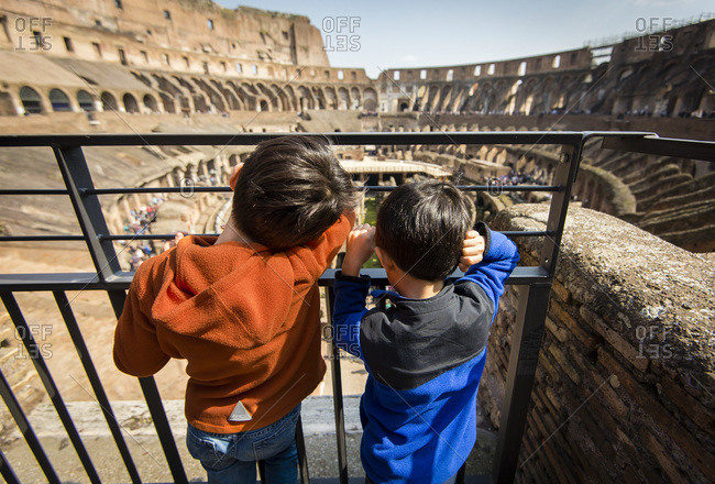 Two young boys overlook Roman Colosseum at railing