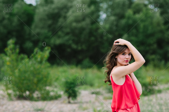 Woman in red poses in a field