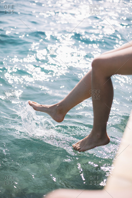 Woman's feet dangling over shimmering water