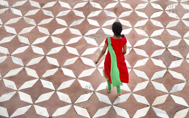 Woman in sari walking across courtyard