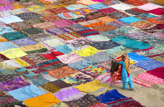 Person laying out washed saris in field
