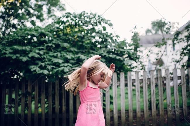 Little girl dancing in a yard