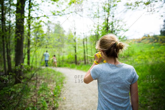 An adolescent girl holding daffodils walks down a path