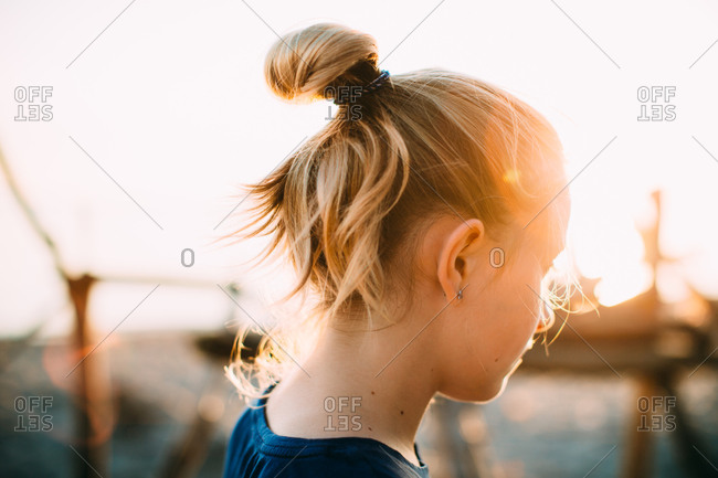 An adolescent girl stands in the setting sun