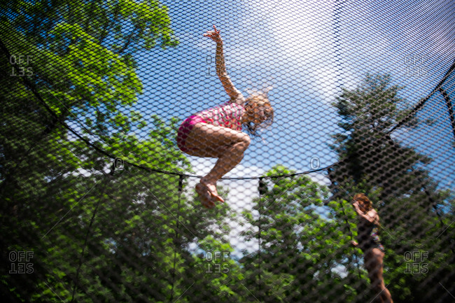 Two girl jump on a backyard trampoline