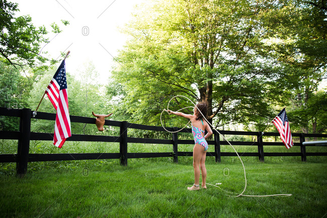 A girl practices using a lasso in her backyard