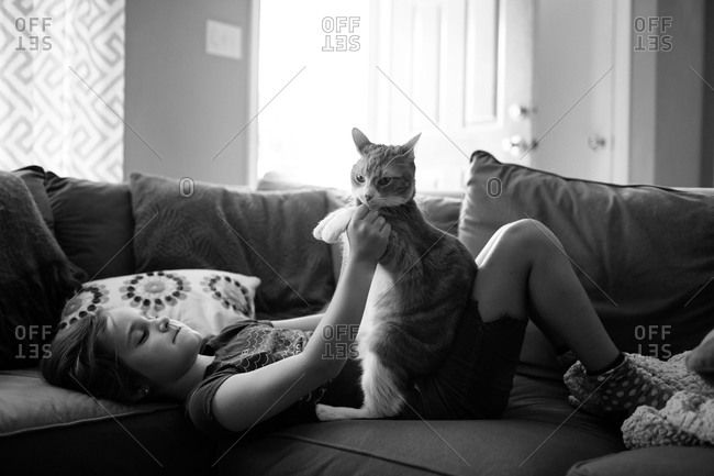 A girl plays with her cat on a  couch