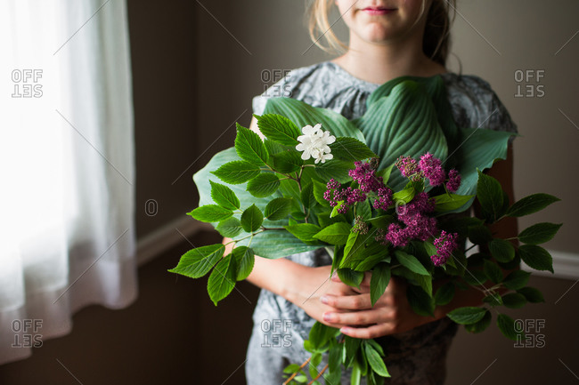 A girl holds a bouquet of leaves and yellow and purple flowers