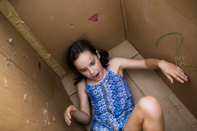 A girl plays in a cardboard box