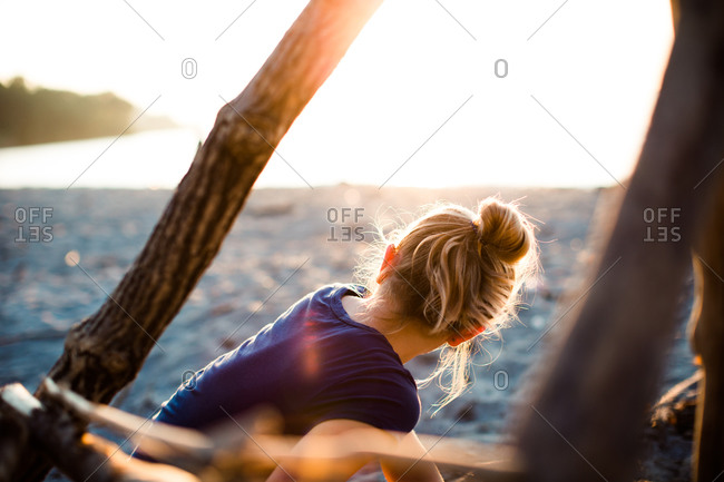 A girl sits on the shore in sunset
