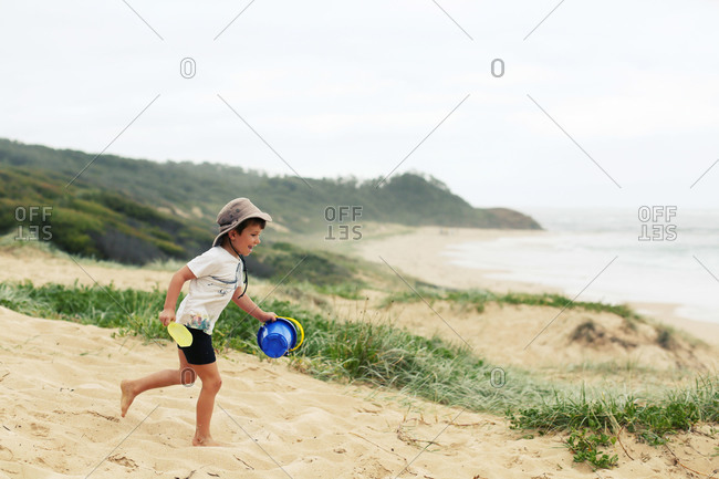 Happy young boy running on beach with pail and shovel