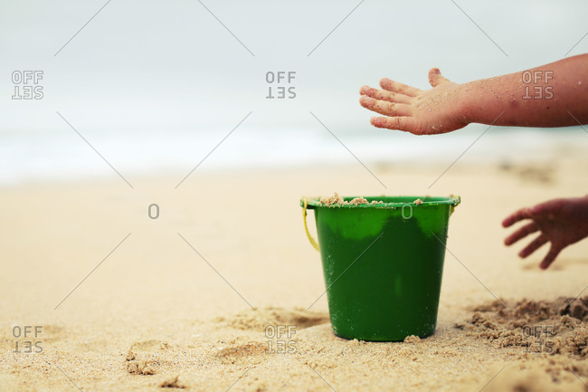Child's hands putting sand in a beach pail