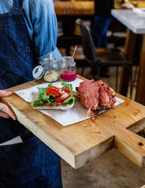 Waiter holding a tray with corned beef sandwich, Tel Aviv, Israel