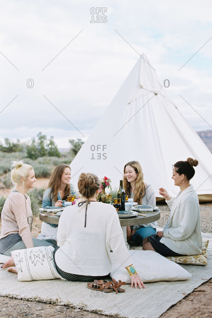 Group of women enjoying an outdoor meal by a teepee in the desert