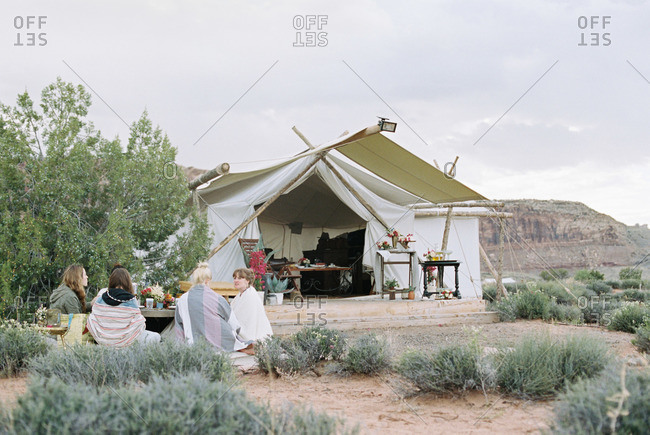 Group of women enjoying an outdoor meal in a desert by a large tent