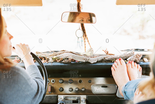 A woman resting her bare feet on the dashboard of a 4x4, on a road trip with another woman driving