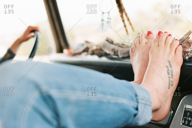 Feet of woman resting her feet on the dashboard of a vehicle