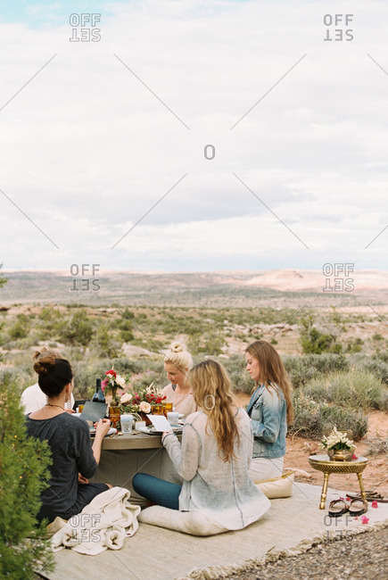 A group of women sitting on the ground round a table in the open desert