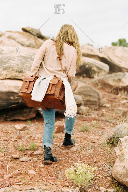 Woman walking past rocks in a desert, carrying a leather bag
