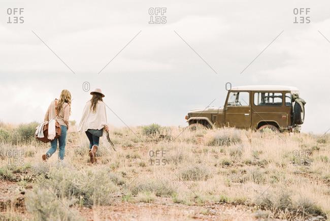 Two women walking towards a 4x4 parked in a desert