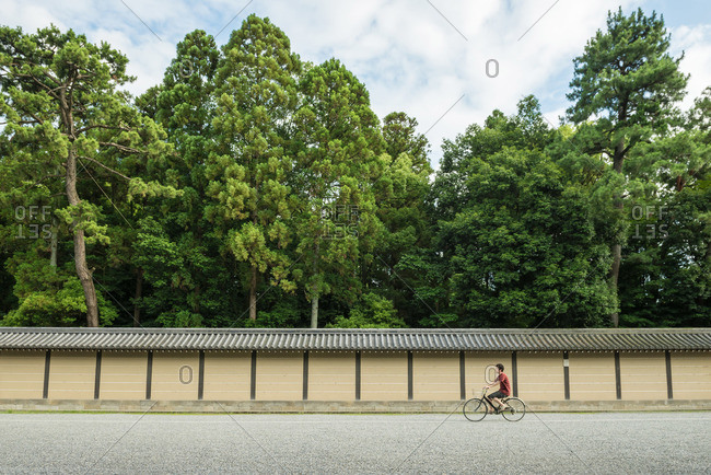 Kyoto, Japan - July 12, 2015: Man riding a bicycle along wall to temple grounds