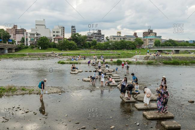 Kyoto, Japan - July 12, 2015: People standing on concrete platforms in Kamo River, Kyoto