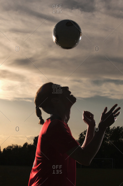 Side view of soccer player heading a ball in field