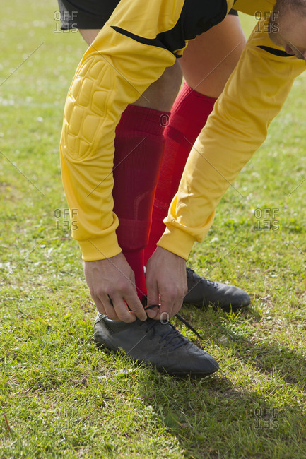 Low section of man tying soccer boot on field